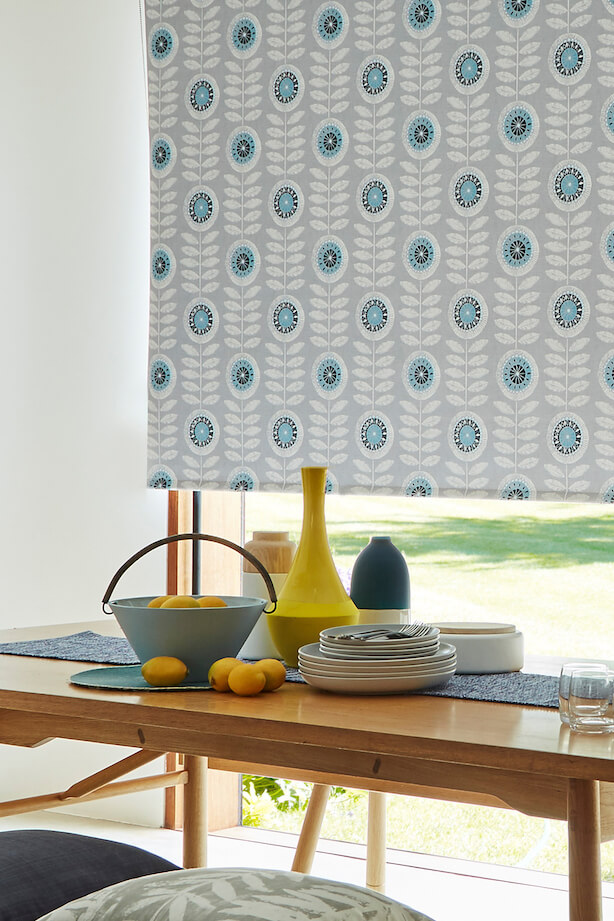 A room with a table in front of a window with a large Hillarys Blackout Roller blind in Neisha Teal fabric